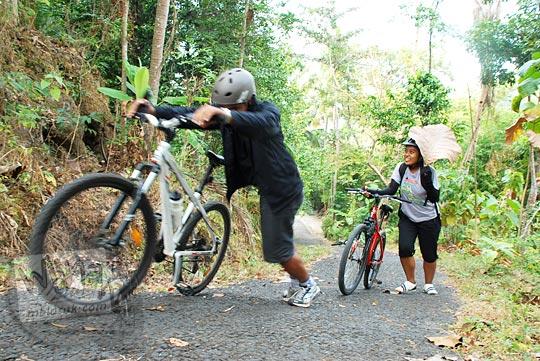 Menuntun sepeda di tanjakan Gua Sriti di daerah Samigaluh, Kulon Progo