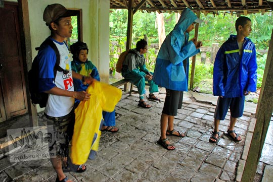 foto sejumlah pemuda mengenakan memakai mantel jas hujan berteduh hujan di teras suatu rumah gaya arsitektur jawa joglo kuno dekat jalan raya wonosari playen paliyan dalam perjalanan ziarah ke gua maria tritis