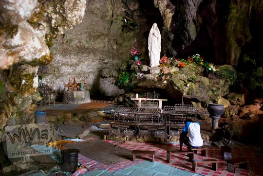 seorang umat pria berdoa menghadap patung bunda maria di dalam suasana pemandangan gua maria tritis paliyan gunungkidul
