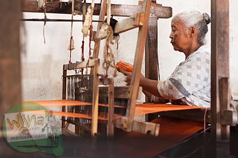 Proses penenunan secara tradisional dengan alat tenun bukan mesin (ATBM) oleh seorang ibu paruh baya di dusun Gamplong, Moyudan, Sleman, Yogyakarta