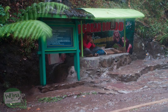 seorang pemuda tukang penjaja jasa foto berteduh di bilik gazebo dekat air terjun coban rondo pujon malang saat hujan deras berkabut