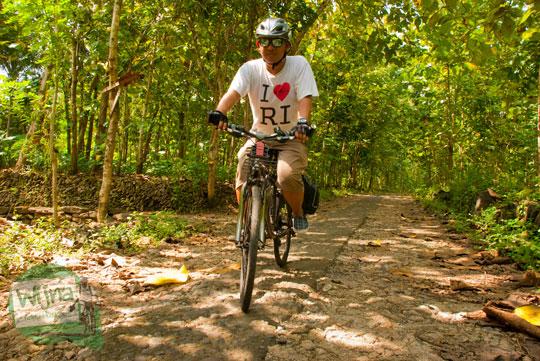 foto pemuda naik sepeda federal baju kaos putih di Yogyakarta memakai kacamata hitam saat perjalanan menuju Curug Banyunibo di desa Sendangsari, Pajangan, Bantul