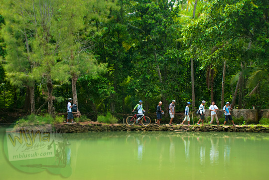 Foto orang-orang berjalan kaki pulang dari pulau di tengah Sendang Ngembel Pajangan Bantul pada tahun 2011