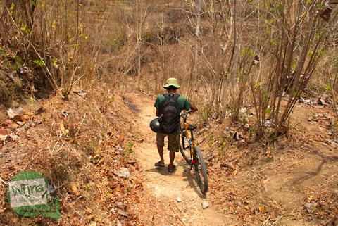 bersepeda menuruni hutan belantara menuju air terjun
