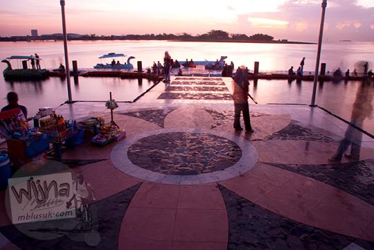 Pedagang asongan dan pengunjung memadati Pantai Losari Makassar di suatu sore hari pada tahun 2012