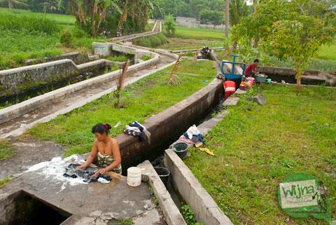 Ibu-ibu dan gadis muda mencuci pakaian di sekitar Umbul Pajangan di Desa Wedomartani, Ngemplak, Sleman, Yogyakarta pada tahun 2012