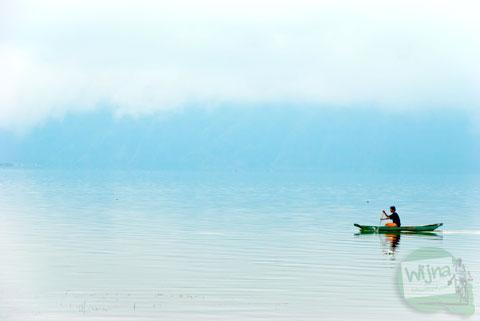 pemandangan seorang warga sedang mengayuh perahu berlatarkan kabut mistis di danau batur, kintamani, Bali