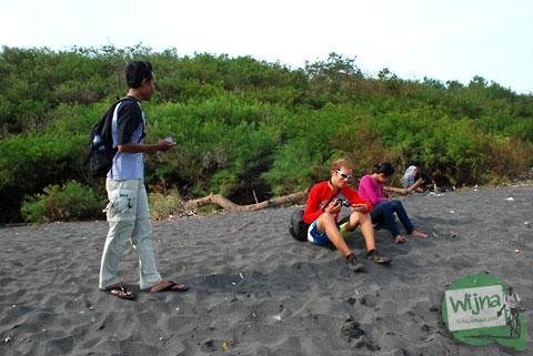 cowok cewek lepas jilbab duduk santai di Pantai Gua Cemara, Bantul