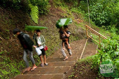 pengunjung cewek wanita kehujanan ketika naik di jalur anak tangga dari dasar curug cimahi sehingga bajunya basah