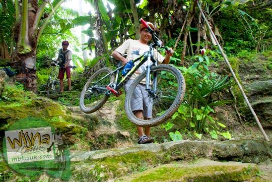 Atraksi pesepeda mengangkat sepeda mereka menuju dasar Curug Pulosari Krebet saat masih sepi