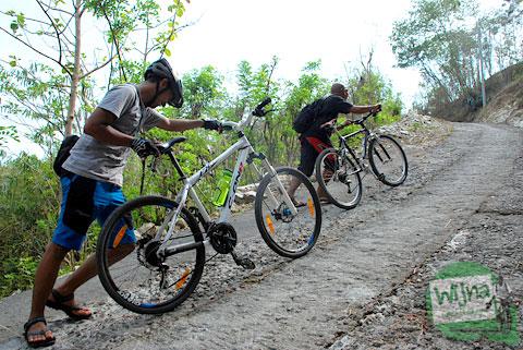 menuntun sepeda melintasi tanjakan klegung yang merupakan rute alternatif menuju nglanggeran tanpa kena macet