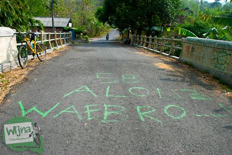 Tulisan peringatan hati-hati saat melintasi jalan tanjakan dalam bahasa jawa yang lucu di bantul, yogyakarta