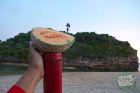 makan buah melon di pantai drini