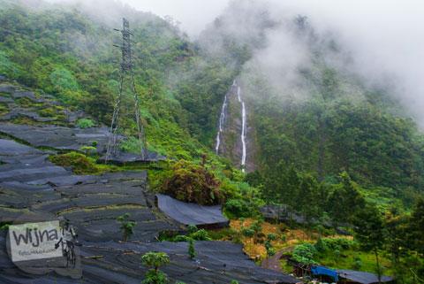 Air Terjun Sikarim di lereng Bukit Sikunir, Dieng terlihat dari kejauhan setelah kabut yang menghalanginya perlahan menghilang