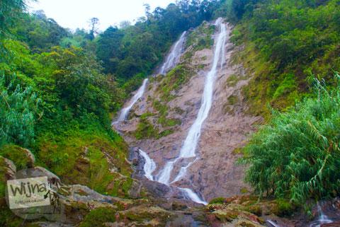 Pemandangan Air Terjun Sikarim yang merambat di lereng bukit Sikunir terlihat indah pada sore hari berkabut