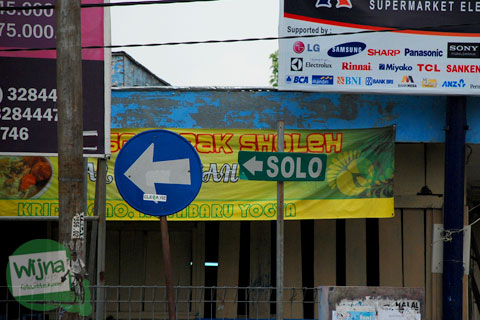 papan petunjuk arah ke Jalan Solo di kota Yogyakarta tertutup spanduk kampanye Haryadi Suyuti