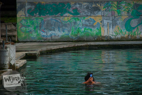 Ibu-ibu telanjang sedang mandi sambil mencuci di Umbul Tirtamulyani di Kebonarum, Klaten