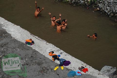 Anak-anak desa bermain air di bawah Jembatan Gantung Kali Boyong