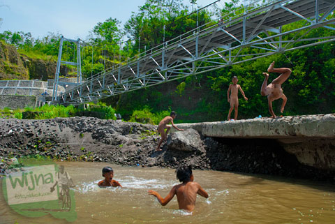 Atraksi anak-anak desa bermain air di bawah Jembatan Gantung Kali Boyong