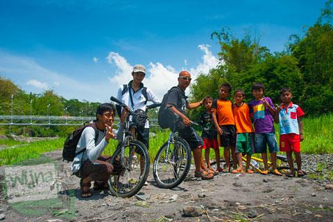 Pesepeda berpose bersama anak-anak desa berlatarkan Jembatan Gantung Kali Boyong