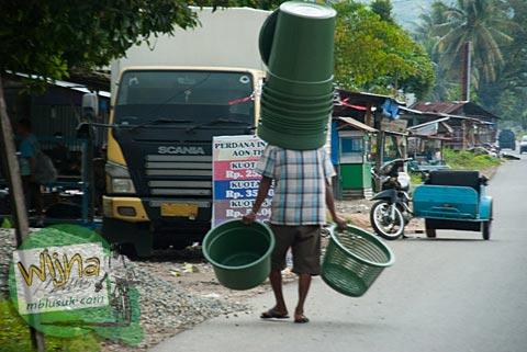 Penjual ember berjalan kaki siang-siang di desa Kuranji, Padang, Sumatra Barat.