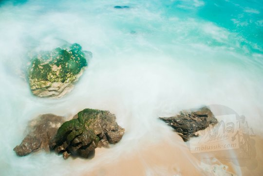 foto slow speed long exposure ombak siang hari dengan batu karang di pantai grojokan banyutibo donoharjo pacitan