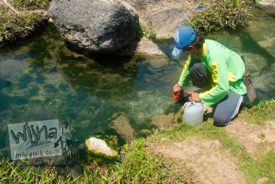 seorang bapak warga pria desa widoro mengambil air dari mata air sungai dengan jerigen di pantai grojokan banyutibo donoharjo pacitan