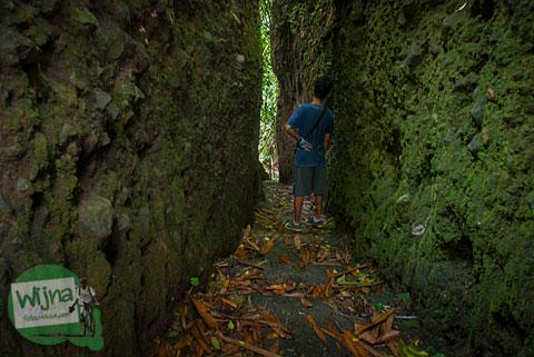 seorang cowok melewati dasar jurang diapit tebing batu dalam perjalanan mencari pancuran dewi peri di desa wisata pentingsari, cangkringan, sleman