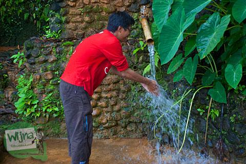 seorang cowok berkaos merah meminum air dari pancuran mistis sendangsari di desa pentingsari, cangkringan, sleman yang memiliki khasiat menyembuhkan penyakit asam urat dan kolesterol