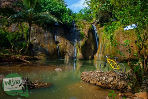 Pemandangan indah cantik Curug Gedhe dengan latar sepeda kuning di Desa Wisata Jurug Taman Sari