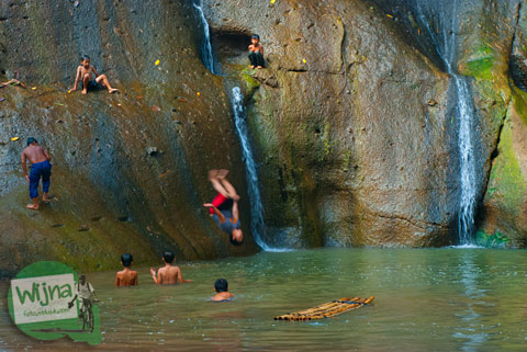 anak-anak bermain lompat mencebur ke dalam kedung air terjun curug Gedhe Lengkongsari di kawasan Desa Wisata Jurug Taman Sari, Semoyo, Pathuk, Gunungkidul