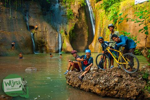 para pesepeda berfoto dengan sepeda dengan latar air terjun Curug Lengkongsari alias Jurug Gedhe di Desa Wisata Jurug Taman Sari, Semoyo, Gunungkidul pasa Awal musim Kemarau