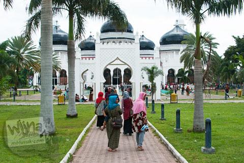 Wisatawan lokal dan jamaah muslim berbondong-bondong memasuki Masjid Baiturrahman Aceh