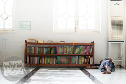 Jamaah pria tertidur di dekat tumpukan al-quran di Masjid Baiturrahman Aceh