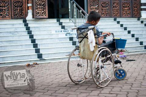 Pengemis tuna daksa dengan kursi roda meminta-minta di Masjid Baiturrahman Aceh