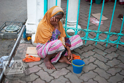 Pengemis wanita tua berjilbab ngantuk di pintu masuk Masjid Baiturrahman Aceh