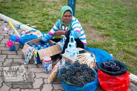 Seorang ibu pedagang asongan yang menjajakan buah di Masjid Baiturrahman Aceh