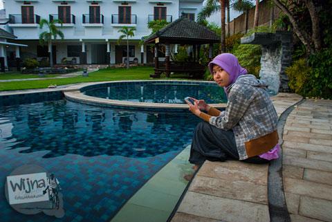 seorang pengunjung bersantai di kolam renang di hotel kota Batu, Jawa Timur