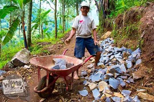 seorang warga mengangkut batu untuk memperbaiki jalan menuju Air Terjun Singokromo, Sawahan, Nganjuk pada tahun 2015