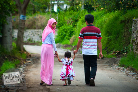 orangtua menggandeng anak mereka di Desa Tulungrejo, kota Batu, Jawa Timur