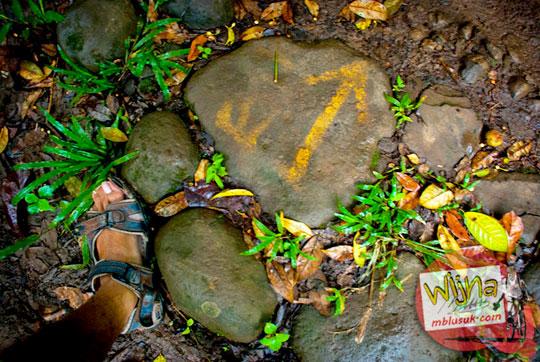 petunjuk cat kuning di batu di dalam hutan yang arahnya ke Air Terjun Kembar Lamuran di Tanggamus, Kotaagung, Lampung pada Maret 2015