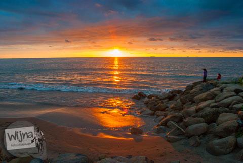 Keindahan pesona matahari terbenam saat senja di Pantai Padang