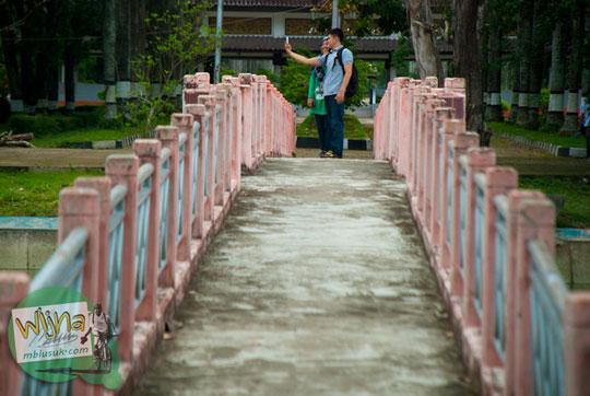 Pasangan cowok cewek berfoto selfie di Jembatan yang ada di lokasi Taman Purbakala Museum Sriwijaya Palembang