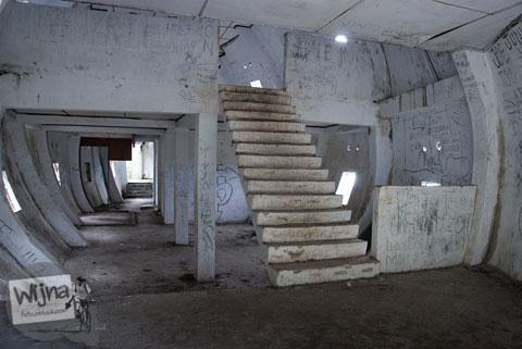 tangga tua di dalam bangunan bekas restoran berbentuk ikan mas di nagari sipolha sumatera utara dekat danau toba