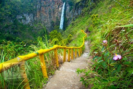 Jalan setapak yang dibatasi tiang kayu dicat kuning menuju dasar Air terjun Sipiso-Piso, Tongging pada tahun 2014
