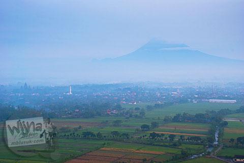Pemandangan Gunung Merapi tertutup awan mendung dari Spot Riyadi, Prambanan, Yogyakarta