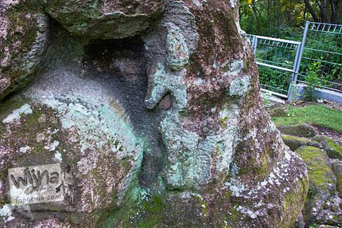 Ukiran relief berwujud manusia pada Arca Ganesha berukuran raksasa yang tersembunyi di dalam hutan Dusun Dawangsari di Prambanan, Yogyakarta