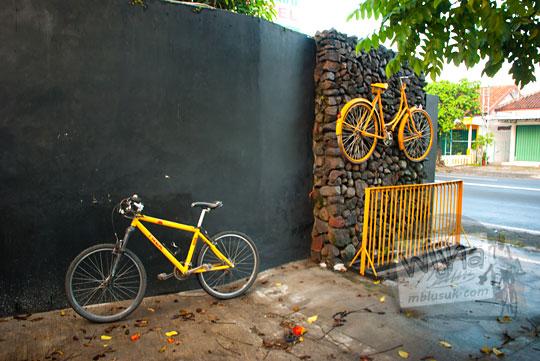 sepeda kuning bersender di tembok rumah