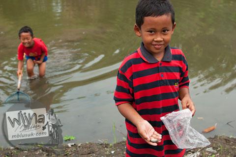 Anak-anak bermain riang gembira di Embung Donomulyo Asri, Gancahan, Godean, Sleman, Yogyakarta