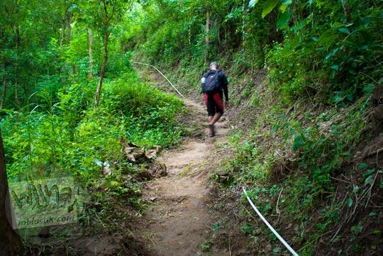 Jalur pipa air pralon putih di dalam hutan yang mengarah ke Grojogan Kali Bulan Bantul saat zaman dulu